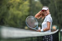 Beautiful girl with a racket on the court stock photo