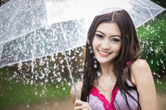 Beautiful girl in the rain with transparent umbrella Stock Image