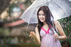 Beautiful girl in the rain with transparent umbrella Stock Photo