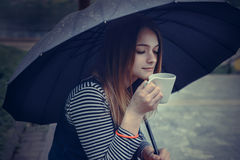 Beautiful girl during a rain under umbrella drinks hot coffee Stock Image