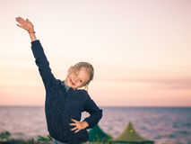 Beautiful girl with raised hand in the background of the sea. Royalty Free Stock Photos