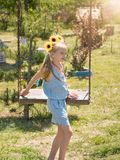 Beautiful girl in the rays of the sun with the decoration of flowers on her head on the old swing. The attraction of the past. Beautiful girl in the rays of the Royalty Free Stock Images