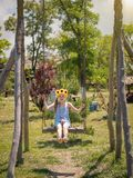 Beautiful little girl with sunflowers on the head swinging on an old swing high. Beautiful girl in the rays of the sun with the decoration of flowers on her Royalty Free Stock Photography