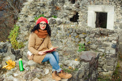 Beautiful girl read book near old castle. Autumn time. Royalty Free Stock Photography