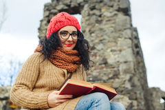 Beautiful girl read book near old castle. Autumn time. Stock Photo