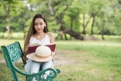 Beautiful girl read book in summer park. Portrait of Asian beautiful brunette woman read text book and sit on garden chair with greenery tree and nature fresh Stock Images