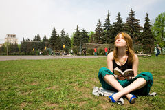 Beautiful girl reading a book. Beautiful girl sitting on grass and reading a book Royalty Free Stock Photography