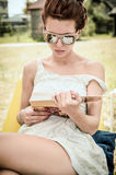 Beautiful girl reading book in beach dress and sunglasses. Beautiful girl reading a book, dressed in beach clothes. The book's reflection can be seen in the stock images