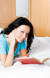 Beautiful girl reading a book on the bed Royalty Free Stock Photos