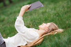Beautiful girl reading book in  blossom garden on a spring day Royalty Free Stock Images
