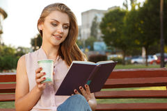 Beautiful girl reading book and drinking coffee Stock Photo