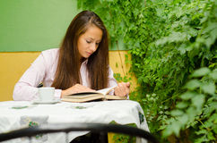 Beautiful girl reading book in the garden Royalty Free Stock Photo