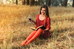 Beautiful girl reading a book with a glass of wine Stock Photography