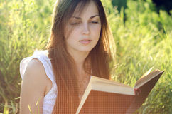 Beautiful girl reading a book on a meadow. Green grass stock photography