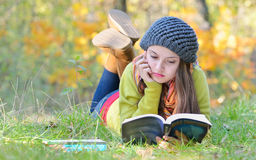Beautiful girl reading a book outdoor royalty free stock photos