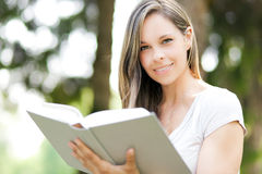 Beautiful girl reading a book outdoor Stock Images