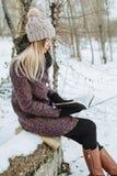 Girl reading book outdoors in winter stock photos