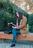Beautiful girl reading book in the park in spring Stock Images