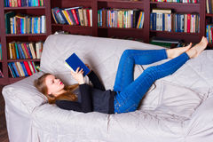 Beautiful girl reading book on sofa Royalty Free Stock Image