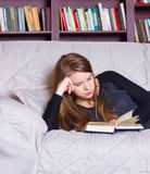 Beautiful girl reading book on sofa Stock Photography