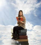 Beautiful Girl Reading a Book on Top of Books Royalty Free Stock Image