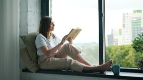 Beautiful girl reading book turning pages sitting on window-sill at home. Beautiful girl student is reading interesting book turning pages sitting on window-sill stock footage