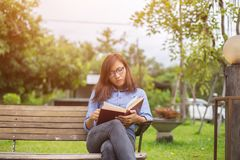 Beautiful girl reading books in the garden royalty free stock image