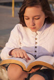 Beautiful girl reading holy bible. On a sun set Royalty Free Stock Photos