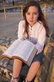 Beautiful girl reading holy bible. On a sun set Royalty Free Stock Photo