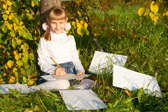 Beautiful  girl reading letter while sitting on Stock Photos