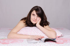 Beautiful girl reading a magazine wondered in bed Stock Image