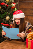 Beautiful girl reading New Year and Christmas congratulation. New Year and Christmas concepts. Happy and beautiful girl in Santa Clause hat reading New Year and Stock Photos
