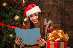 Beautiful girl reading New Year and Christmas congratulation. New Year and Christmas concepts. Beautiful girl reading New Year and Christmas congratulation from Royalty Free Stock Image