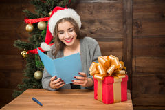 Beautiful girl reading New Year and Christmas congratulation. Happy smiling girl holding postcard and reading New Year and Christmas congratulation. Someone sent Royalty Free Stock Photos