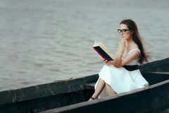 Retro Woman Reading a Book in a Vintage Boat. Beautiful girl reading a novel in an old fisherman boat Royalty Free Stock Photos