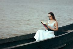 Retro Woman Reading a Book in a Vintage Boat. Beautiful girl reading a novel in an old fisherman boat Royalty Free Stock Image