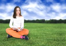 Beautiful girl reading outdoors Royalty Free Stock Photo