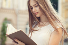 Beautiful girl reading outdoors Stock Photo