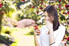 Beautiful girl reading text message on her smart phone in the ga Stock Images