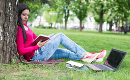 Beautiful girl reads book in a park Royalty Free Stock Photos