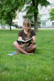 Beautiful girl reads book in a park Stock Photo