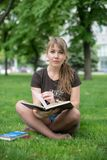 Beautiful girl reads book in a park Stock Photography