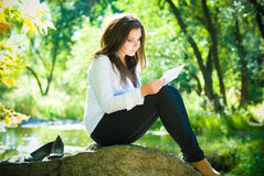 Beautiful girl reads a letter near garden lake Royalty Free Stock Photography