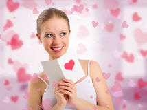 Beautiful girl reads a postcard valentine. On abstract background with pink hearts royalty free stock image