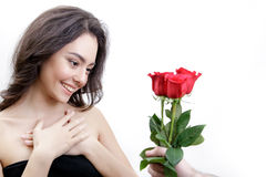 Beautiful girl receives three red roses. She is surprised, looking at the flowers and smiling. Royalty Free Stock Image