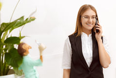 Beautiful girl at reception answering the call. Beautiful girl at the reception desk answering the call in dental office Stock Photo