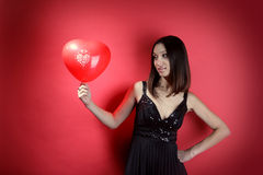 Beautiful girl with a red balloon in the form of h Royalty Free Stock Photo