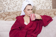 Beautiful girl in red bathrobe drinking coffee Stock Photos