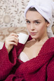 Beautiful girl in red bathrobe drinking coffee in the bed Stock Photo