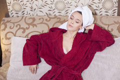 Beautiful girl in a red bathrobe relaxing Royalty Free Stock Photo